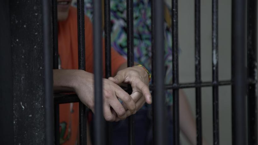 Mãos femininas sobre grades de uma cela prisional