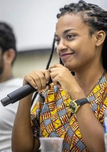 Mulher negra de tranças, de perfil sorri com enquanto segura um microfone com duas mãos. Tem um relógio preto na mao esquerda.